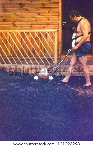 Vintage photo of father with baby daughter in baby carrier mowing grass (1981)