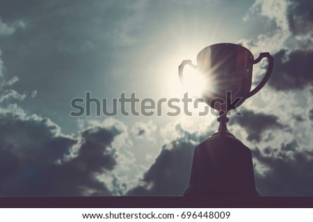 Vintage photo of Golden trophy with dark sky background with copy space ready for your design , Conception of victory in the competition. #696448009