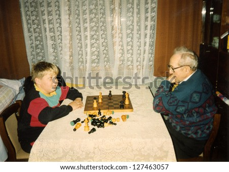 Vintage photo of grandfather and grandson playing chess (early eighties)