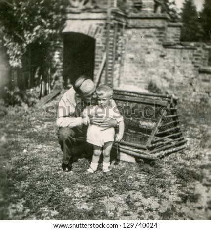 Vintage photo of grandfather and little grandson outdoor (forties)