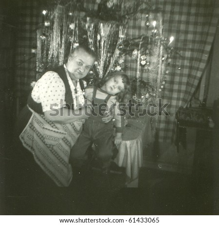 Vintage photo of grandmother and granddaughter under Christmas tree (fifties)