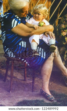 Vintage photo of grandmother with baby granddaughter (1982)