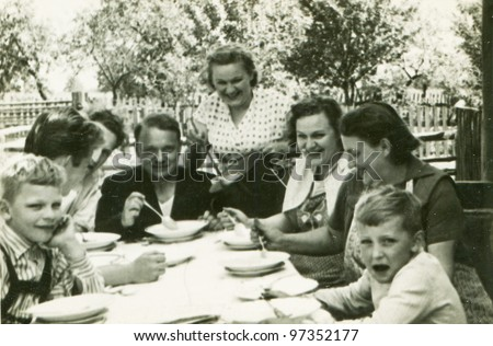 Vintage photo of happy family dining outdoor (fifties)