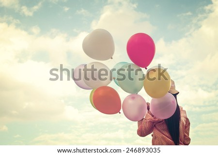 Vintage photo of  Happy young girl  holding colorful balloons and flying on clouds sky background.