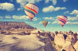 Vintage photo of hot air balloon flying over rock landscape at Cappadocia Turkey.
