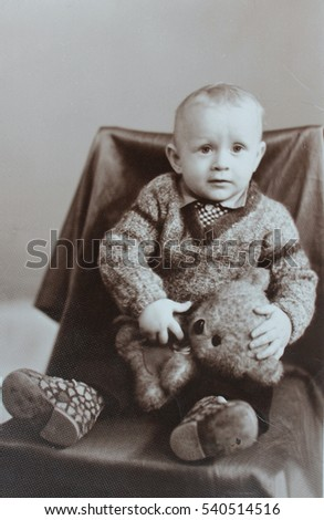 Vintage photo of little cute boy sitting in the chair with a bear (early1980's)