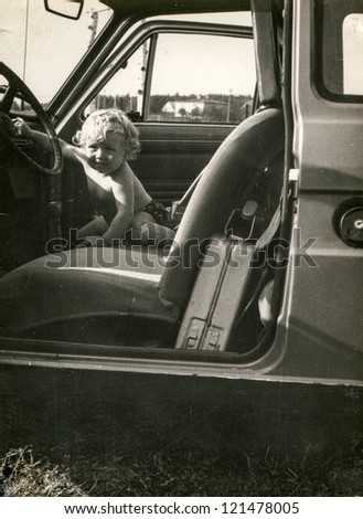 Vintage photo of little girl in a car (early eighties)
