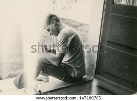 Vintage photo of man sitting on doorstep, forties