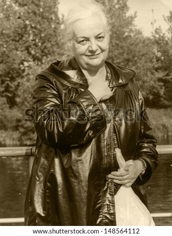 Vintage photo of mature woman in raincoat (seventies)