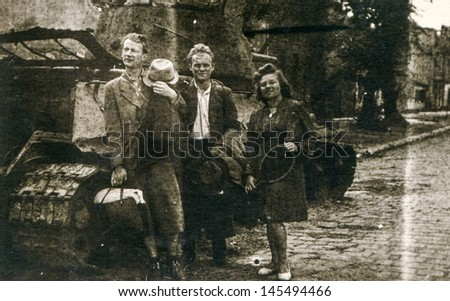 Vintage photo of men and woman posing in front of tank during WWII in Poland, forties