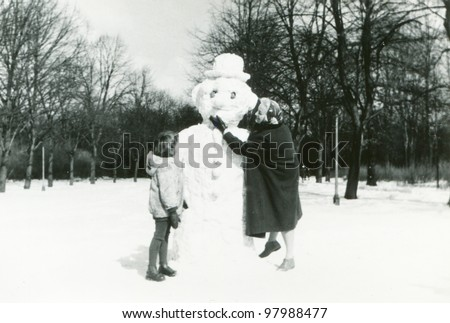 Vintage photo of mother and daughter building a snowman (fifties)