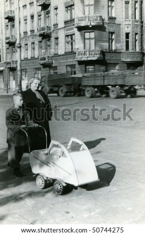 Vintage photo of mother with a son and a baby in pushchair (1954)