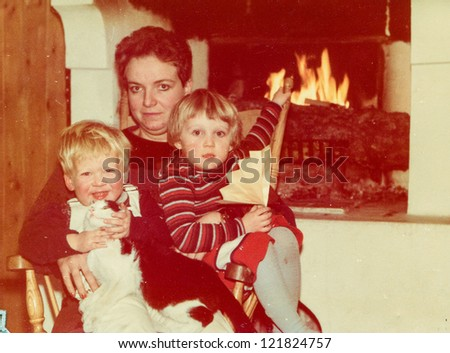 Vintage photo of mother with little children and cat near fireplace (early eighties)