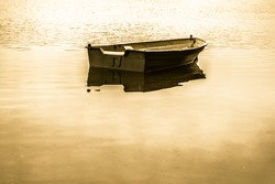 Vintage photo of old boat for fishing on the lake, quiet surface of water. Nature background, vintage effect.