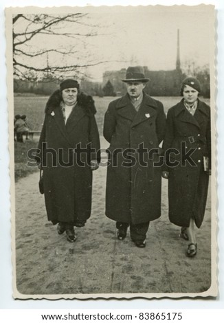 Vintage photo of  parents and daughter walking on the street (thirties)