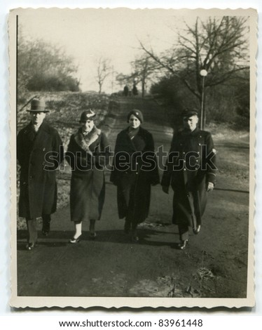 Vintage photo of  parents, son and daughter walking on the street (thirties)