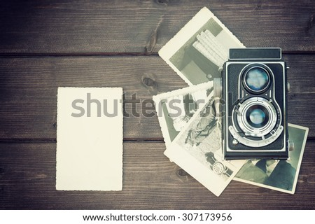 Vintage photo of the old blank photo is lying on a wooden desk  in the left  edge of the photo. On the right side of the photo is laying old camera on an old photos. All  trademarks are removed.