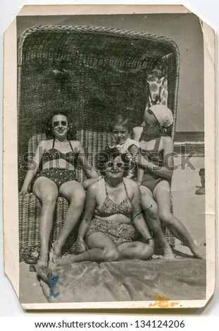 Vintage photo of three-generation family in beach basket, fifties