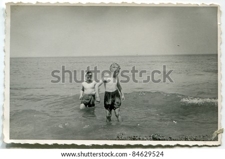 Vintage photo of two brothers bathing in the sea (fifties)