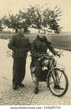 Vintage photo of two men with a motorbike, forties