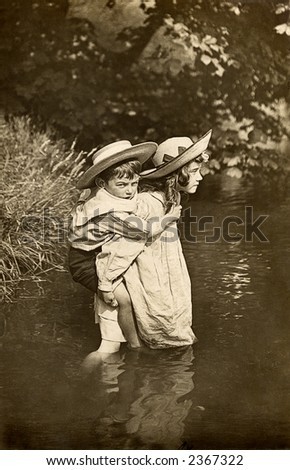 Vintage photo of two small children crossing a stream - stock photo