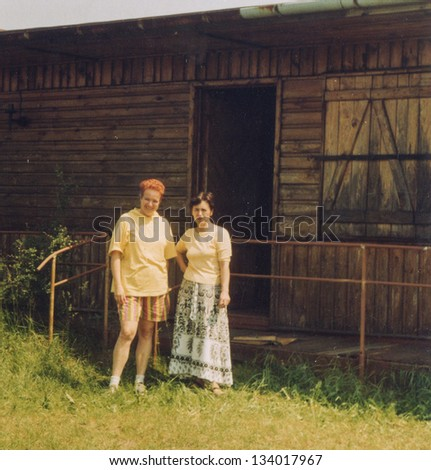 Vintage photo of two women in front of summer cottage (seventies)