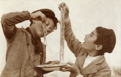 Vintage Photo of two young boys eating spaghetti with their hands