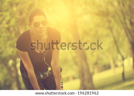Vintage photo of woman listening music in park after running