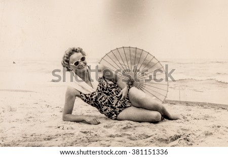 Vintage photo of woman resting on beach in swimsuit with umbrella (early 1960's)