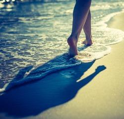 Vintage photo of woman's legs walking by sea shore. Close up of sea shore with woman walking through waves.