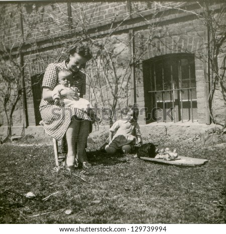 Vintage photo of woman, two little children, hen and chicks (forties)
