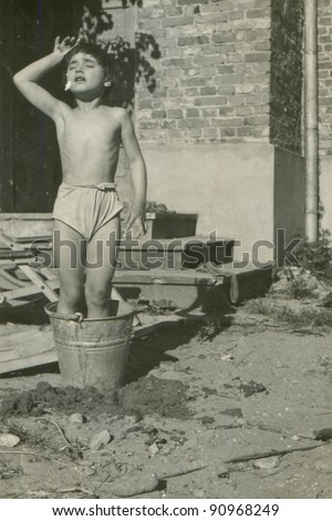 Vintage photo of young girl bathing in a bucket(fifties)