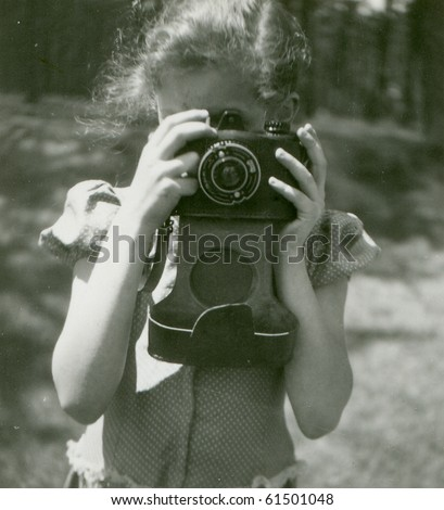 Vintage photo of young girl with camera (fifties)