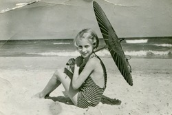 Vintage photo of young girl with umbrella on beach (fifties)