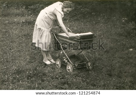 Vintage photo of young mother with pram (1981)
