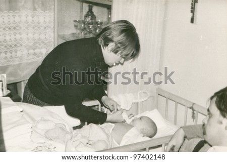 Vintage photo of young parents with a baby son (early eighties) - stock photo