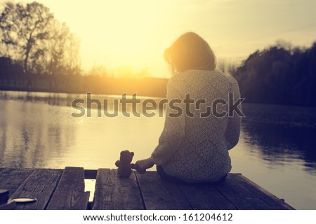 Vintage Photo Of Young Woman Sitting On Pier With Her Teddy Bear