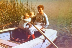 Vintage photo (scanned reversal film) of mother with little children on rowing boat, early eighties