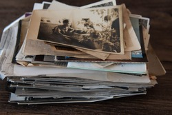 Vintage photo stack, old family photos on a dark wooden background. Memoirs
