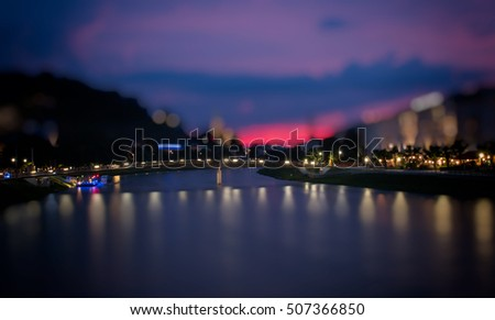 Vintage photo. Walk evening on curve river in Salzburg, Austria, Europe. View city, far mountains. Blue, purple night sky. Evening lights city. Retro poster image. Type street Spain, France, Italy