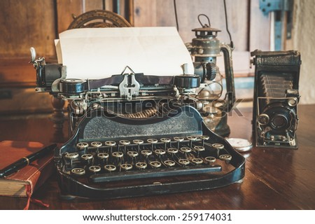 vintage photography still life with typewriter, folding camera, globe map and book on a wood table. #259174031