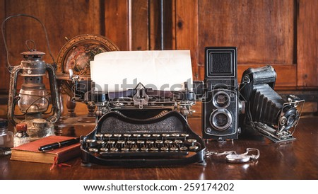 vintage photography still life with typewriter, folding camera, globe map and book on a wood table. #259174202