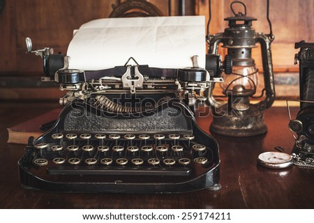 vintage photography still life with typewriter, folding camera, globe map and book on a wood table. #259174211