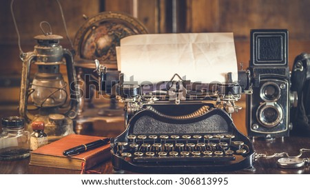 vintage photography still life with typewriter, folding camera, globe map and book on a wood table. #306813995
