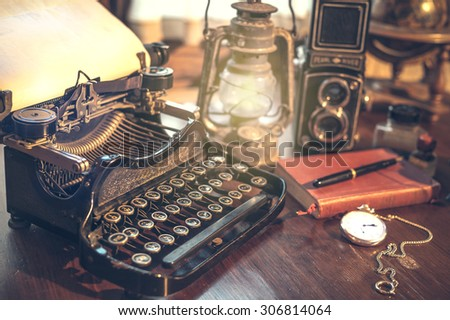 vintage photography still life with typewriter, folding camera, globe map and book on a wood table. #306814064