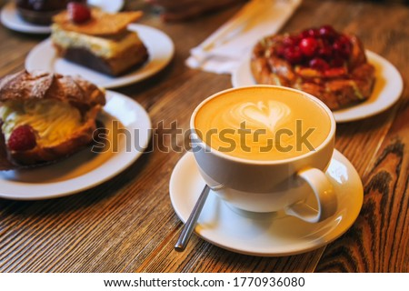 Vintage photography style of Coffee and desserts pastry, puffs, tarts, cakes on wooden table top, selected focus.
