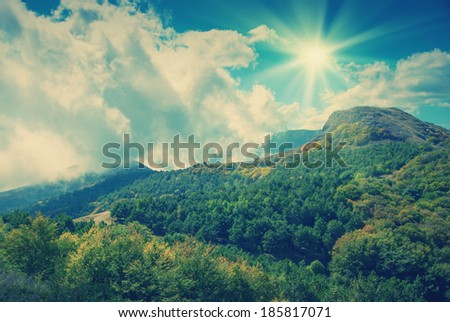 Vintage picture. Mountain landscape with clouds, lying on a hillside
