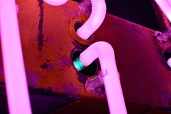 Vintage pink neon sign with glass tubes and flaking paint