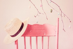 Vintage pink painted chair with a straw hat and branch with wood