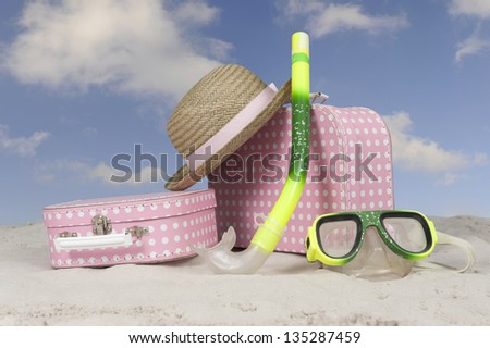 vintage pink with white dots suitcase and straw summer hat at the beach